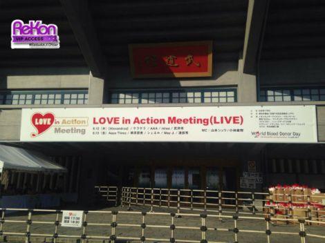 Spanduk LOVE in Action Meeting di Nippon Budokan. Di kanan bawah, terlihat tumpukan goodies untuk penonton. (Baca artikel di bawah)