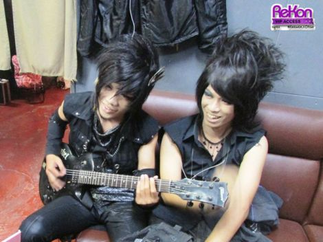Guitarist Hanzo and bassist Aga relaxing backstage before their performance.